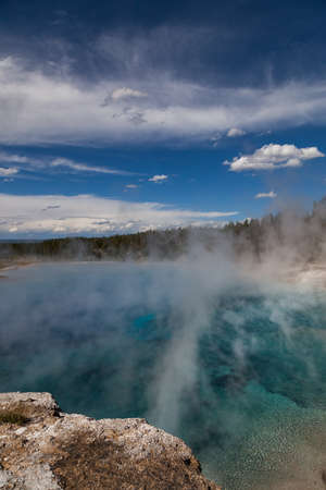 Excelsior Geyser's blue geothermal water with white steam rising up past a rim of tall trees and into the blue sky with white clouds at Yellowstone national Park.