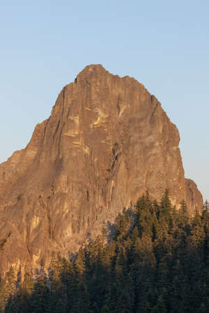 One ear of the Rabbit Ears ancient volcanic feature in the Southern Oregon Cascade Mountains lit by glowing afternoon sunshine with smoke in the background sky. 版權商用圖片