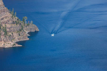 A tour boat takes people around the the magnificently blue and deep Crater Lake located in the Southern Oregon Cascade Mountains.