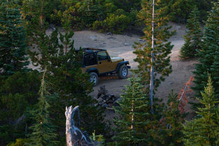 Red Blanket Mountain near Prospect, Oregon / USA - September 8, 2014: A gold Jeep Rubicon sits at the end of a dirt road surrounded by trees at the top of Red Blanket Mountain near Prospect, Oregon.