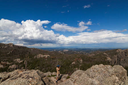 A photographer stands on a granite rock formation taking pictures with a dynamic landscape background in Custer State Park, South Dakota.