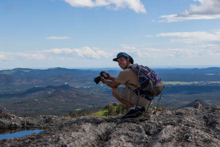 A smiling photographer perched on a rock cliff with a landscape view of the Black Hills of South Dakota behind him.