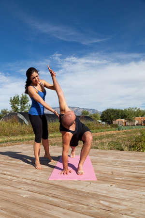 A yoga instructor gives tips to a student at an outdoor afternoon yoga class that is held on a wooden platform at a farm. 版權商用圖片