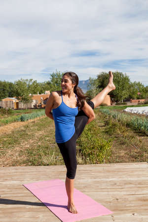 A yoga instructor holds an intricate pose of flexibility and balance at an outdoor afternoon yoga class at a farm.