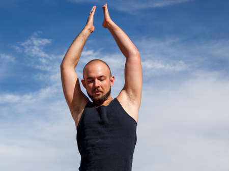 A man doing a yoga pose on a sunny afternoon with bright sunshine and a background of blue sky and wispy clouds. 版權商用圖片