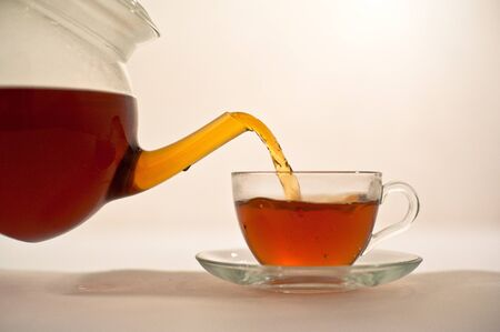 Hot tea is poured into a glass cup