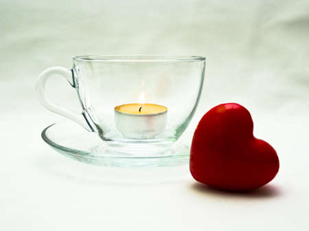 Still life wiht glass cup and red heart and candle