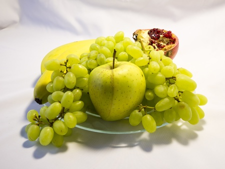Still life with grapes, apple and banana on white background Stock Photo