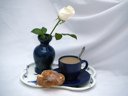 Wite rose in a blue vase and a cup of coffee with cakes photo