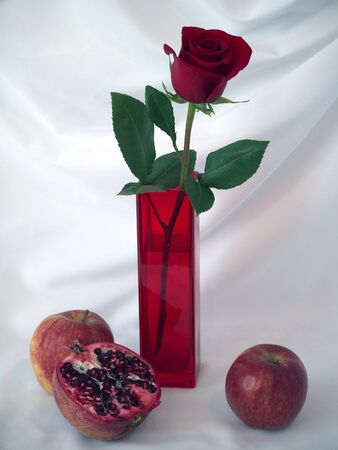 Red rose in a red vase with apples and a pomegranate