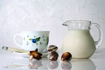 White cup, milk and sweets on white background Stock Photo