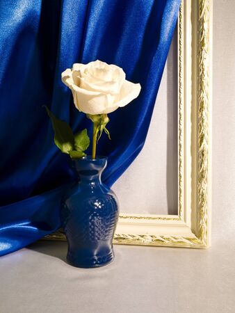 Rose in a glass vase a background of curtains and frames photo