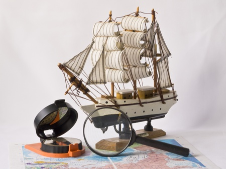 wold map: Yacht, a compass and magnifying glass on the wold map Stock Photo