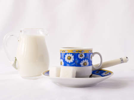 Cup, milk and sugar on white background Stock Photo