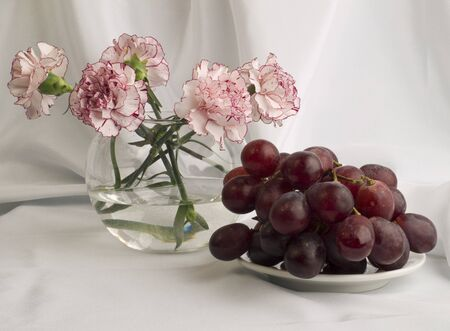 Beautiful bouquet of delicate pinks and juicy grapes on the white background