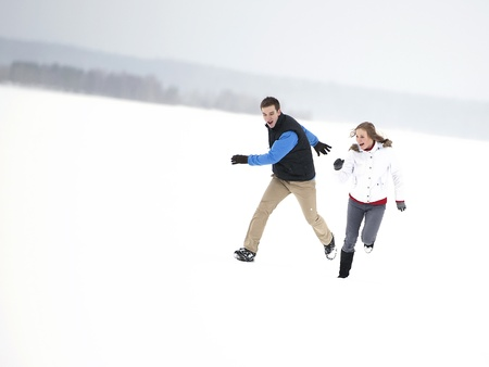 Young happy couple running through a snowy field Stock Photo
