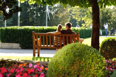 Young couple sitting on a bench in the park photo