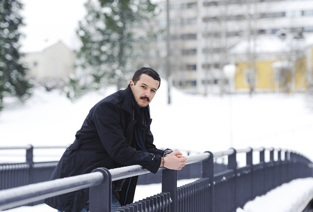 Portrait of a handsome young man on the bridge in winter photo