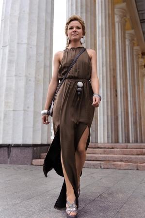 maxi dress: A girl walks along marble columns