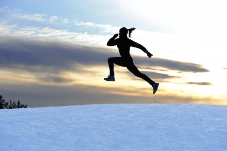 Female athlete running outdoors in winter Stock Photo