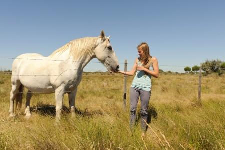 okşayarak: çitin arkasında atı okşayarak kız