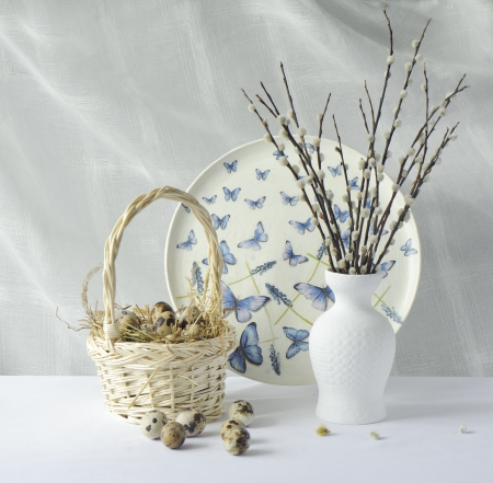 Quail eggs in a basket on hay and willow branches in a white vase Stock Photo - 18890976