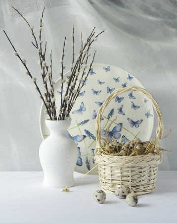 Quail eggs in a basket on hay and willow branches in a white vase