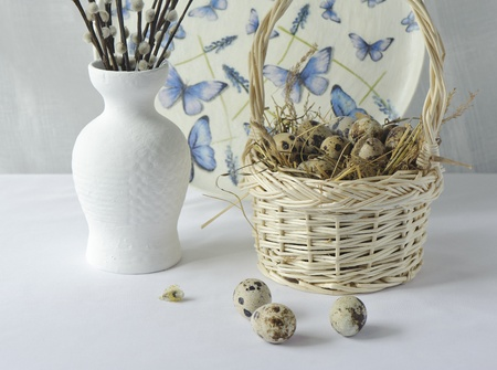 Quail eggs in a basket on hay and willow branches in a white vase Stock Photo - 18890974