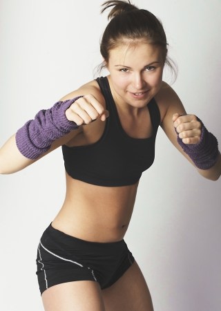 Young sports attractive woman showing boxing motion in the studio