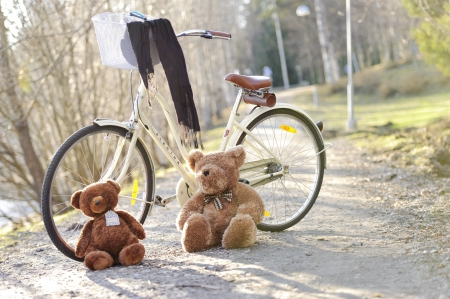 A bike standing in the park on a path in a sunny day with toys two bears light Stock Photo