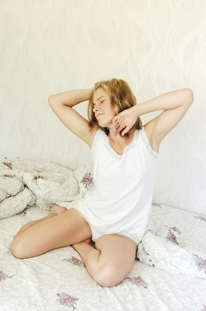 Sleepy woman waking with stretch sitting in bed