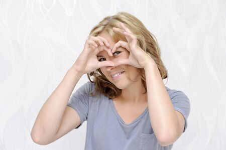 pleasantness: Smiling young woman making heart with fingers Stock Photo