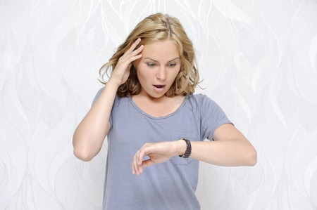 Young woman looking at her watch being late Stock Photo