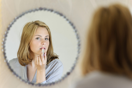 Beautiful young woman doing make-up Stock Photo