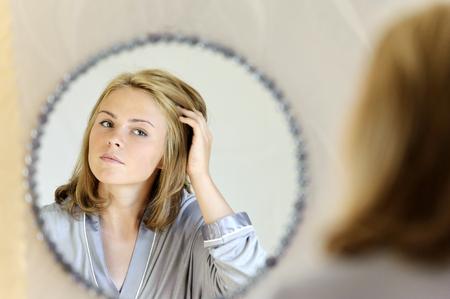 Beautiful young woman doing hair