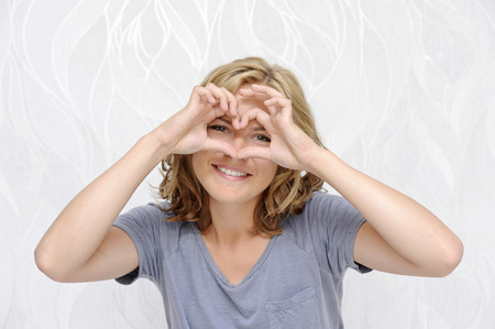 Smiling young woman making heart with fingers Stock Photo