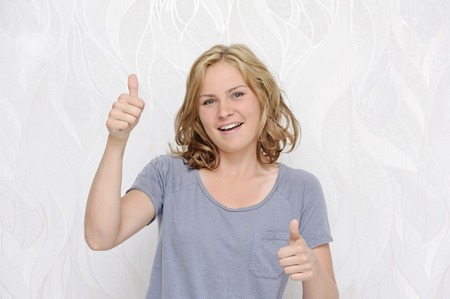 Young smiling woman showing thumbs up Stock Photo