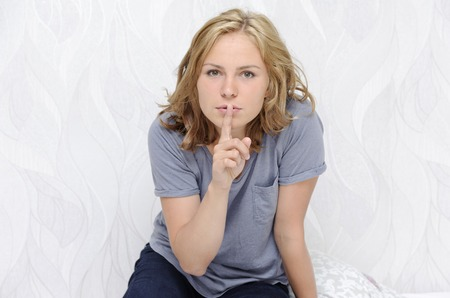 Young woman showing a hush sign