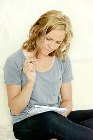 Young woman thinking over making notes in notebook Stock Photo