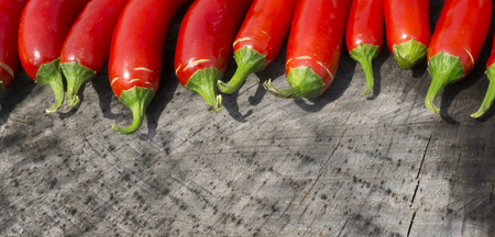 serrano: Colorful Red Serrano Peppers on a Wood Background