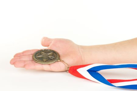 Childs hand holding a medal on white background.