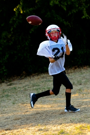 builds: Young football player about to catch the football. Stock Photo