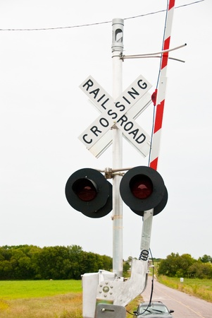 railway transportation: Railroad crossing sign on a country road with gate up.
