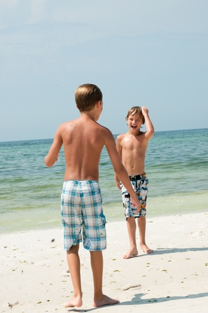 Two boys having fun on the beach. photo
