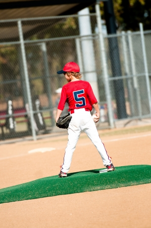 Young boy in red jersey standing on pitching mound about to pitch.