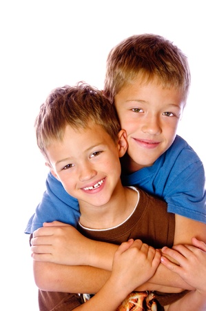 whote: Two young boys hugging each other very happy; isolated on white