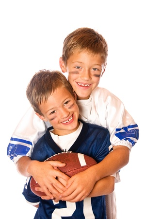 brotherly love: Two cute young boys in jerseys holding a football   Isolated on white
