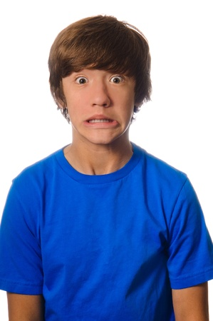 Scared teen with wide opened eyes wearing a blue shirt.  Isolated on white background. Stock Photo