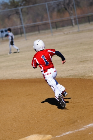 Little league youth baseball player round first base. photo