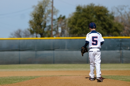 Little league baseball player taking the mound to pitch. photo